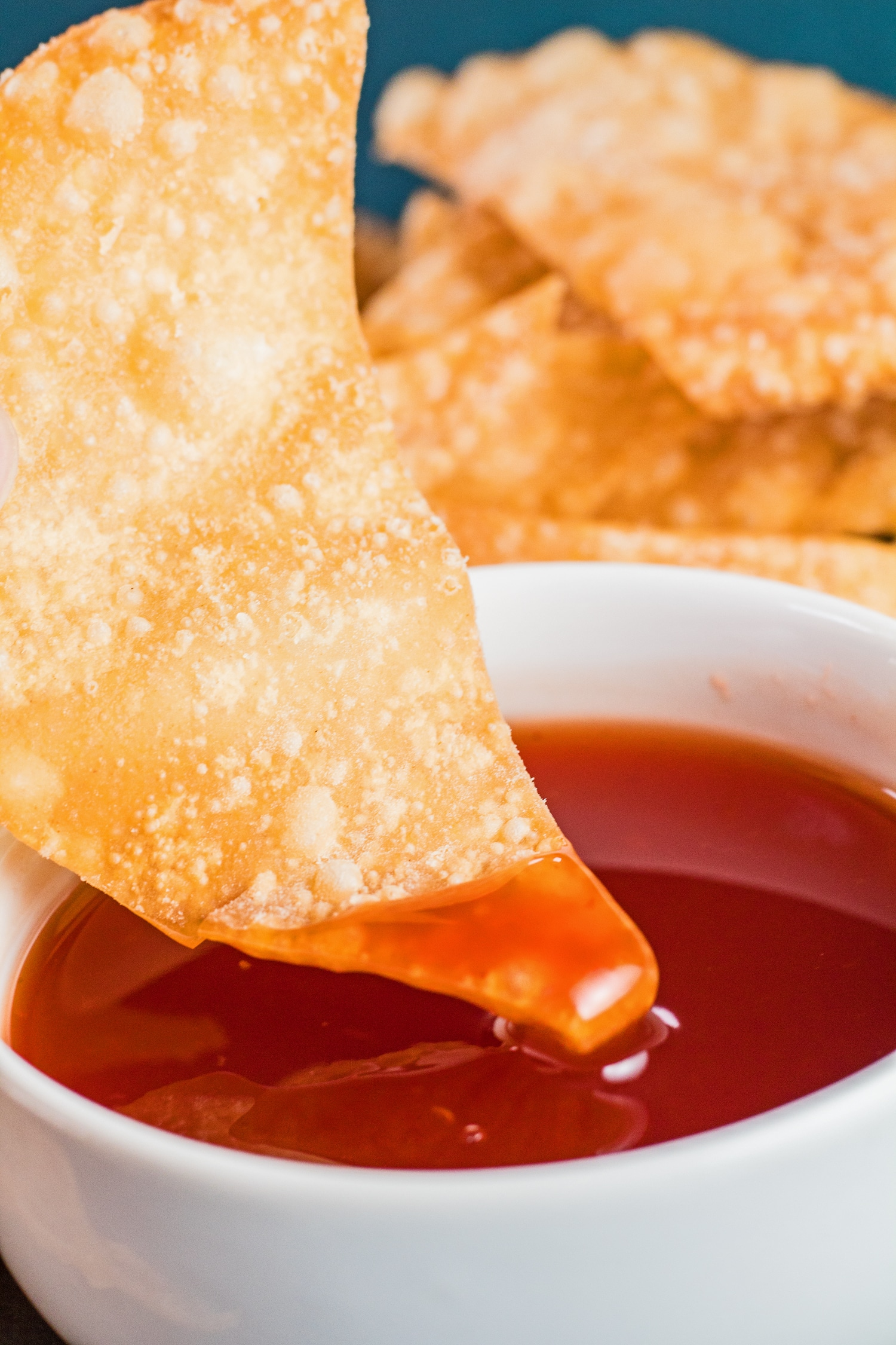 tall closeup of a fried wonton being dipped into the bowl of sweet and sour sauce.