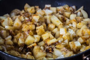 pan fried potatoes after cooking with a cover on and being turned to finish frying.