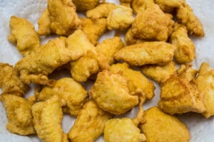 Tiernos trozos de pollo frito al wok listos para ser mezclados con la cremosa salsa de coco.