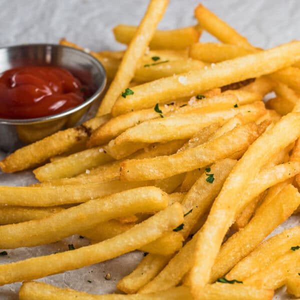 Large square image of air fryer frozen french fries served with ketchup.