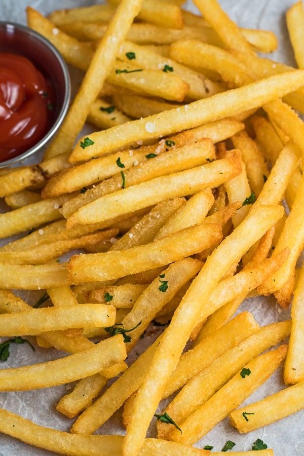 Vue aérienne inclinée de la friteuse à air frites congelées servies avec du sel et du ketchup.