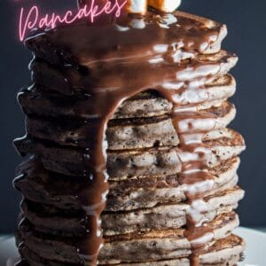 pin with tall image of stacked chocolate pancakes on dark background.