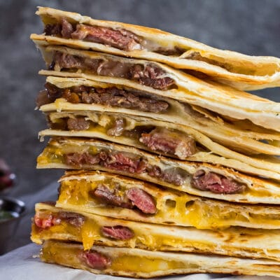 large square image of stacked leftover prime rib quesadillas with condiments in background.