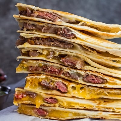 small square image of stacked leftover prime rib quesadillas with condiments in background.