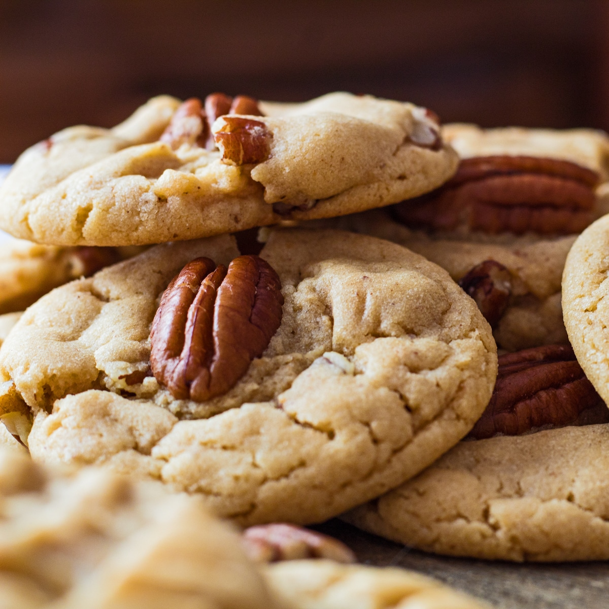 Large square image of loosely piled peanut butter pecan cookies.