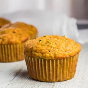 large square image of pumpkin zucchini muffins on light background.