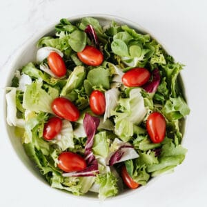 Simple green salad side dish for prime rib in white bowl.