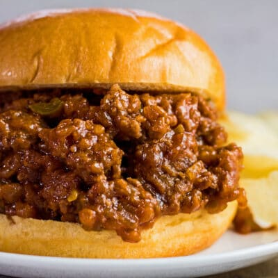 large square closeup image of sloppy joes on buns with chips.