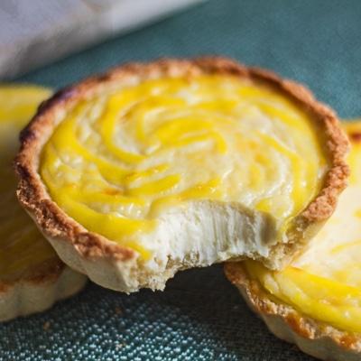 Petite image gros plan carré des tartes au fromage hokkaido avec une morsure montrant la texture crémeuse.