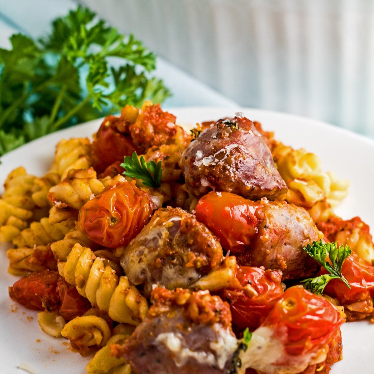 Large square angled side view of the Italian Sausage Bake served on white plate.