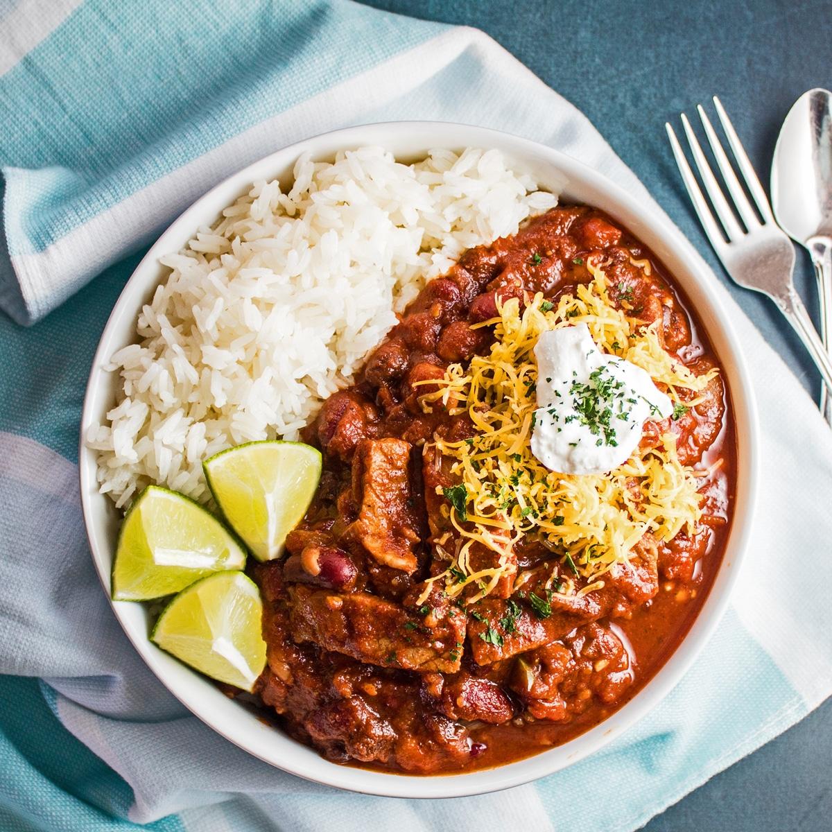 großer quadratischer Kopf von Prime Rib Chili, serviert mit Reis in einer weißen Schüssel.