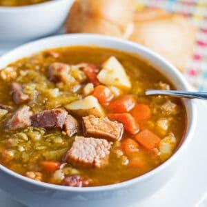stort firkantet vinklet overheadbillede af sopa de chicharos serveret i hvid skål.