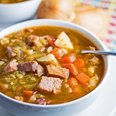lille firkantet vinklet overheadbillede af sopa de chicharos serveret i hvid skål.