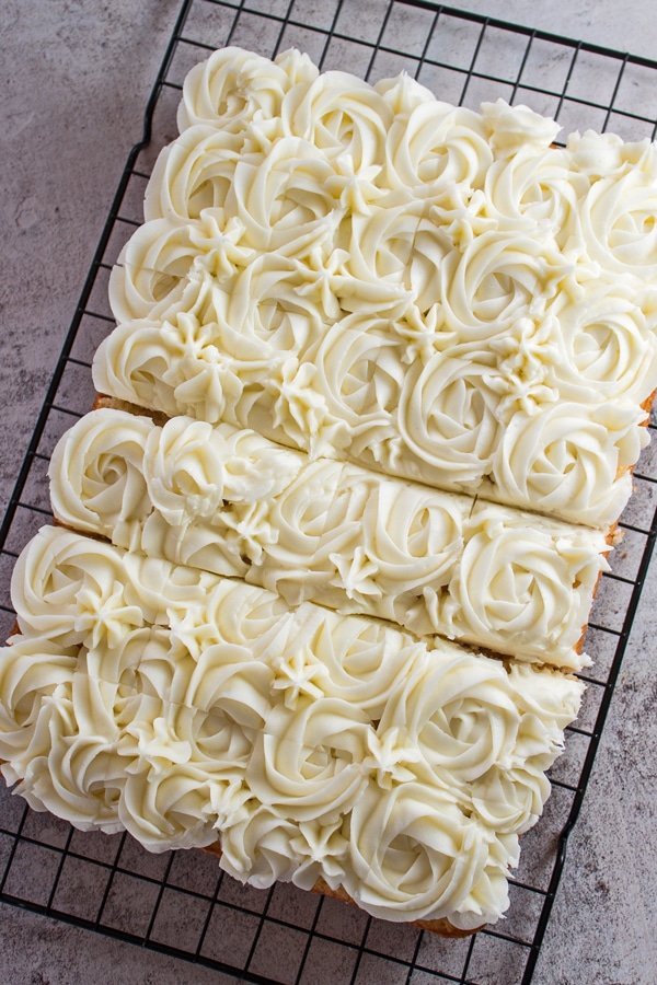 tall overhead image of frosted vanilla tray bake sheet cake.