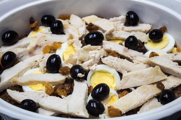 layering the cooked chicken breast meat, raisins, and olives.