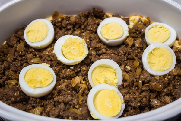 layering the seasoned beef and hard-boiled eggs into the casserole.