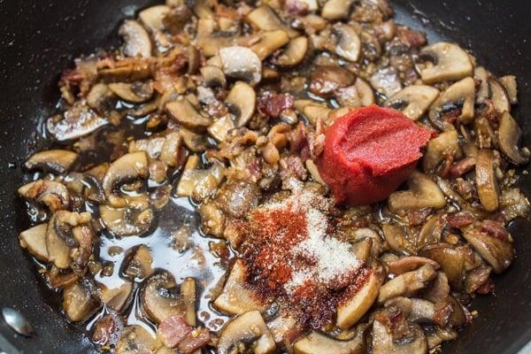champiñones salteados y tocino con condimento y pasta de tomate.