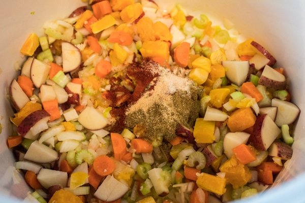 seasoning cumin paprika salt pepper added to vegetables for sopa de chicharos.