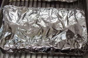 smoked beef back ribs wrapped securely in aluminum foil.