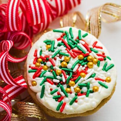 रिबनमधील ख्रिसमस कुकीजची मोठी चौरस ओव्हरहेड प्रतिमा.