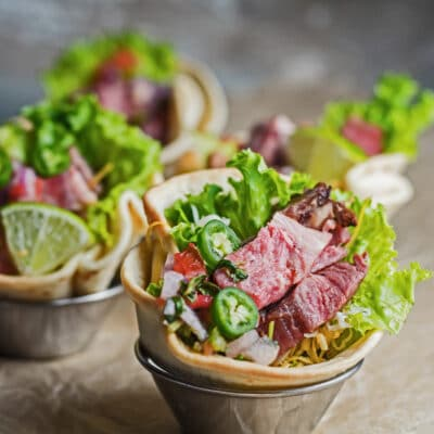 large square angled frontview of the leftover prime rib tostadas in metal dipping sauce cups.