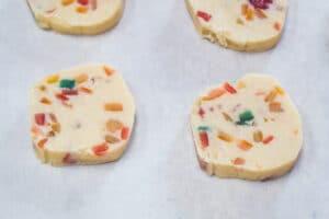 sliced fruitcake shortbread cookies on baking sheet.