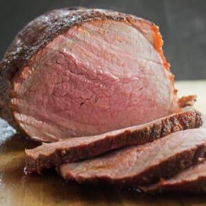 imagen cuadrada grande del perfecto asado de res ahumado cortado en rodajas y listo para servir.