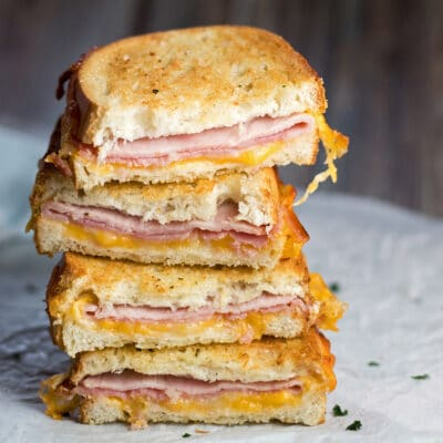 large square image of stacked halves of crispy, cheesy Air Fryer Grilled Ham and Cheese sandwiches.
