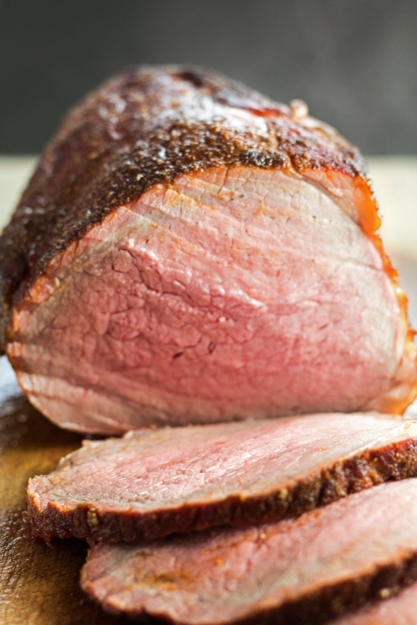 tall image of sliced smoked beef roast.