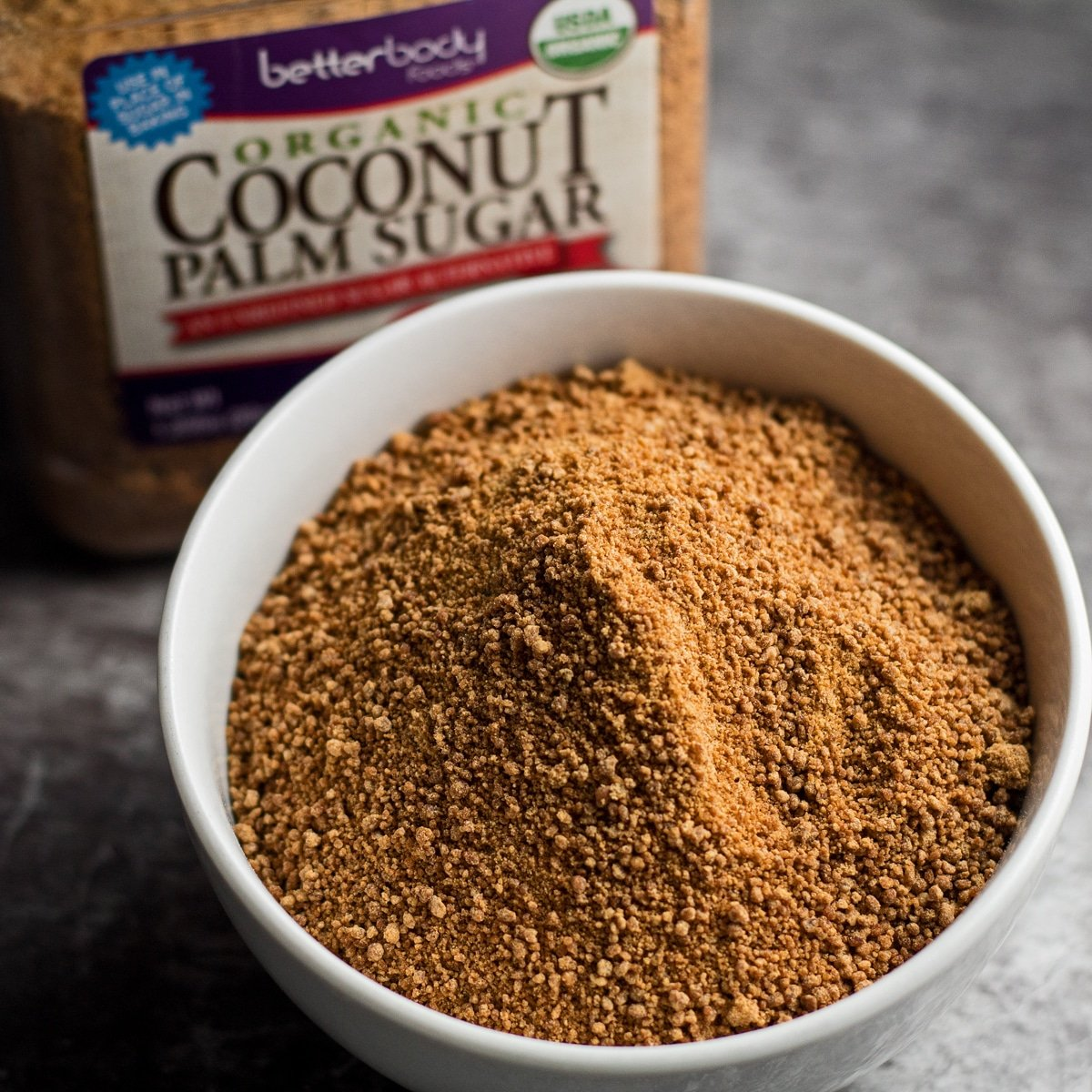 Large square coconut sugar in a bowl with packaging in background.