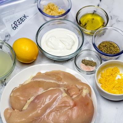 Greek Chicken Marinade ingredients and chicken ready to combine.