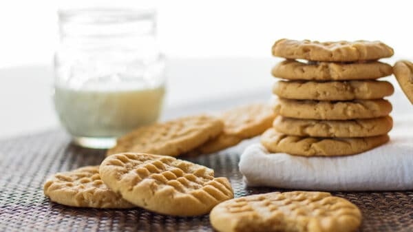wide image of stacked peanut butter cookies served with a glass of milk.