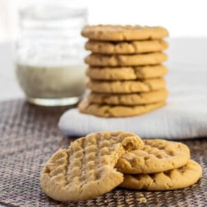 large square peanut butter cookies served with a glass of milk.