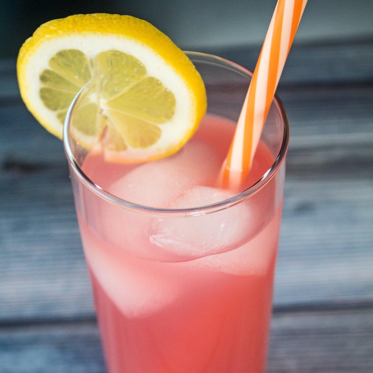 large square pink vodka lemonade served with a lemon slice.