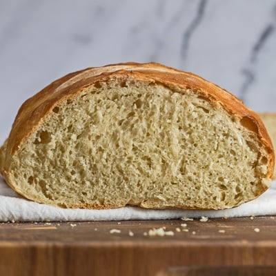 rustic bread loaf sliced open on wooden cutting board.