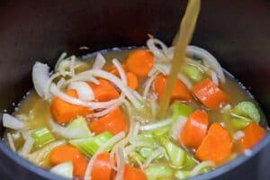 tilsæt kylling bouillon til madlavning med grøntsagerne til basesuppesmag.