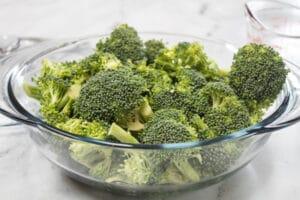 Broccoliblommor i mikrovågssäker skål med vatten.