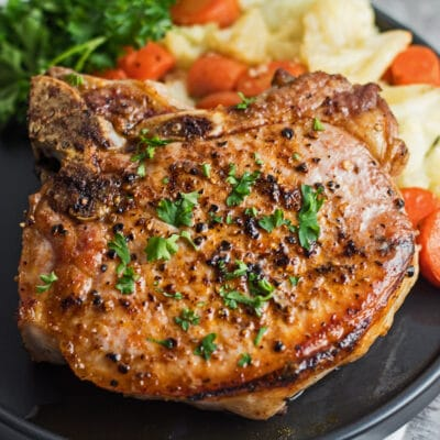 Large square image of cast iron pork chops on black plate.