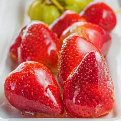 grote afbeelding tanghulu aardbeien en meer op dienblad.