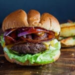 Large image of Wagyu beef burger with fried potato wedges in background.