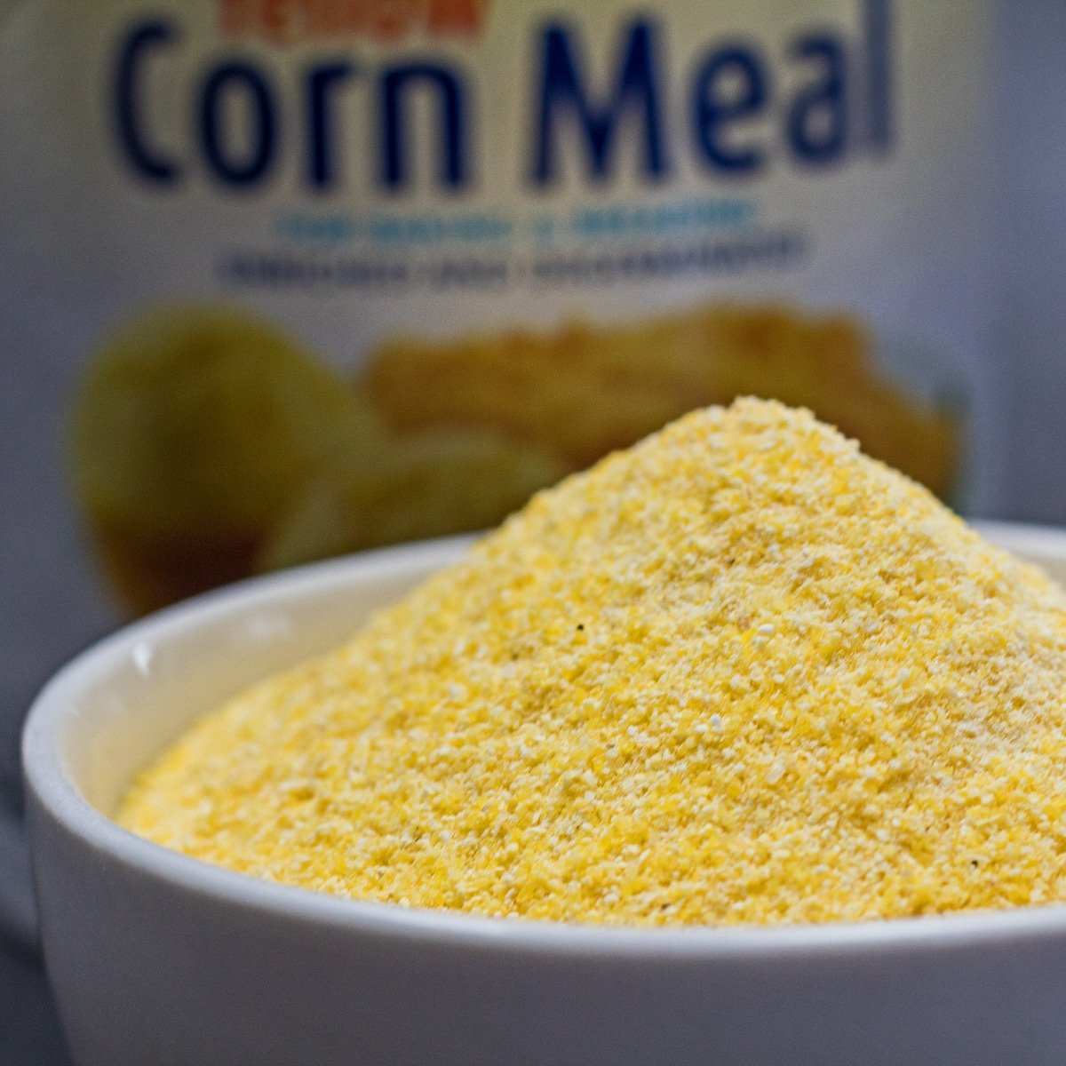 Large square image of yellow cornmeal in white bowl.