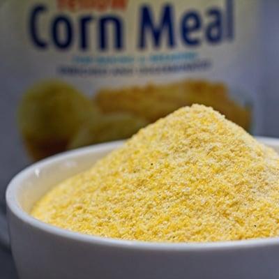 Imej persegi tepung jagung kuning dalam mangkuk putih.