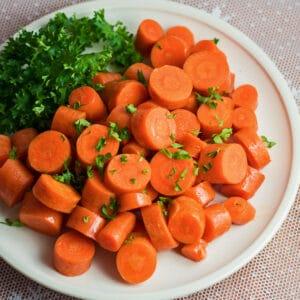 Stor firkantet overhead af mikrobølgeovn gulerødder med persille garnering.