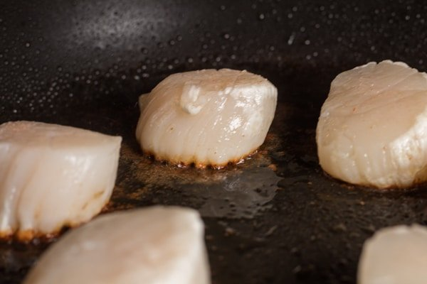 Sea scallops with the first side seared and ready to flip.