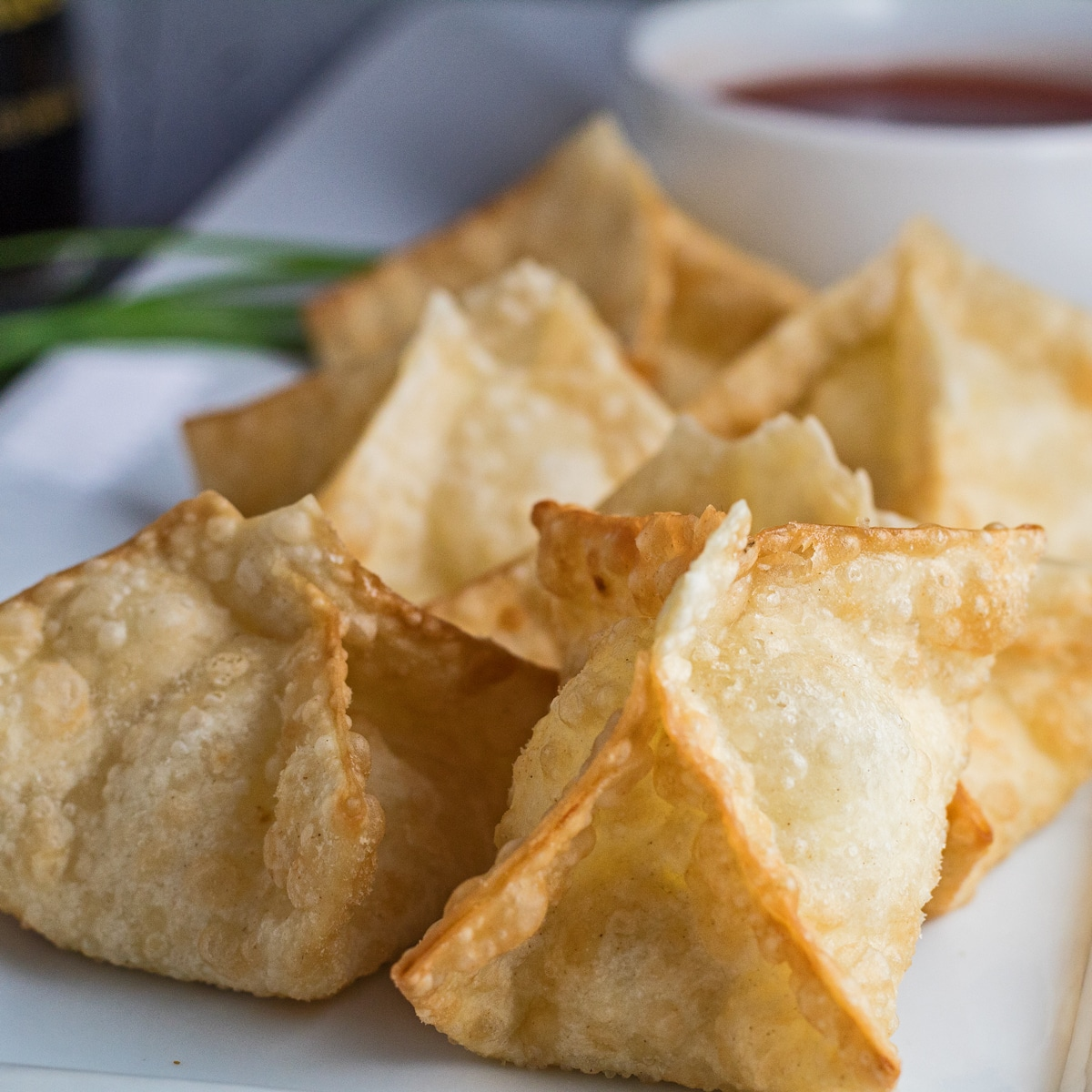 Fried crab rangoons on white plate with sweet n sour sauce.