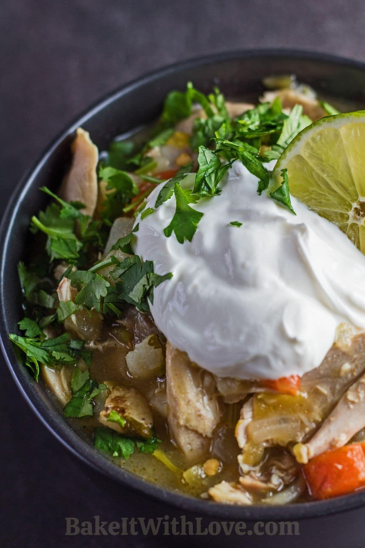 Green chile chicken stew topped with sour cream and cilantro in black bowl.
