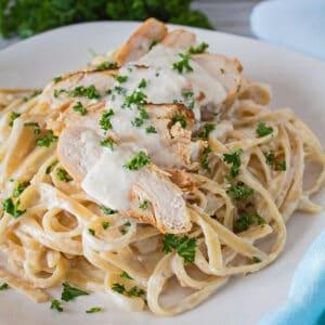 Fettuccine alfredo de pollo a la parrilla con pollo en rodajas servido sobre pasta.