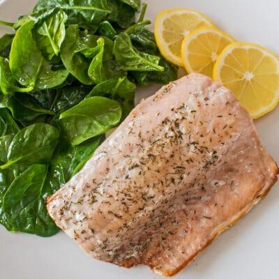 Обжаренный на сковороде лосось, подается с увядшей зеленью и дольками лимона.