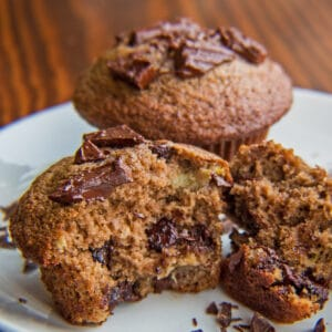 Protein powder chocolate banana muffins with one split open in front.