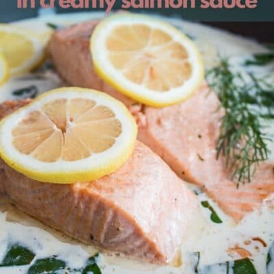 Salmon in white wine sauce served in cast iron skillet with text overlay.